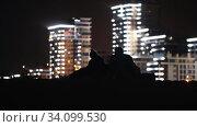 Купить «Young man and woman sitting on the beach at night on the background of glowing modern buildings and talking to each other», видеоролик № 34099530, снято 7 июля 2020 г. (c) Константин Шишкин / Фотобанк Лори