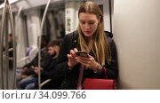 Купить «Positive young woman absorbed in her smartphone while traveling in subway car», видеоролик № 34099766, снято 17 января 2020 г. (c) Яков Филимонов / Фотобанк Лори