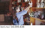 Купить «Portrait of young female customer visiting pottery shop», видеоролик № 34099838, снято 3 июля 2020 г. (c) Яков Филимонов / Фотобанк Лори