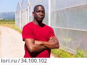 Confident african american farmer outdoors near greenhouse. Стоковое фото, фотограф Яков Филимонов / Фотобанк Лори
