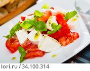 Купить «Caprese salad with fresh tomatoes, mozzarella cheese and basilic herb», фото № 34100314, снято 11 июля 2020 г. (c) Яков Филимонов / Фотобанк Лори