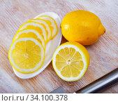 Купить «Sliced lemons on wooden table», фото № 34100378, снято 10 июля 2020 г. (c) Яков Филимонов / Фотобанк Лори