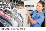 Купить «Young woman working in modern dry cleaner», фото № 34100914, снято 9 мая 2018 г. (c) Яков Филимонов / Фотобанк Лори