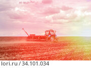 Купить «Russia Samara May 2020: Spring. Sowing work. A tractor with a seeder trailer works in the field at sunset.», фото № 34101034, снято 11 мая 2020 г. (c) Акиньшин Владимир / Фотобанк Лори