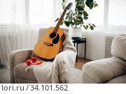 Купить «Guitar and headphones on white armchair, nobody», фото № 34101562, снято 20 июня 2020 г. (c) Tryapitsyn Sergiy / Фотобанк Лори