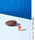 Купить «Toy plastic astronaut on a light ground with stone and shadows against blue starry sky background. Place for text. Outer space concept.», фото № 34109482, снято 5 июля 2020 г. (c) easy Fotostock / Фотобанк Лори
