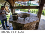 Well in Moldovita Monastery - Romanian Orthodox monastery located in commune of Vatra Moldovitei, Suceava County, Romania. (2019 год). Редакционное фото, фотограф Konrad Zelazowski / age Fotostock / Фотобанк Лори