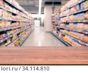 Купить «Brown wooden board empty table in front of blurred background. Perspective dark wood over blur in supermarket - can be used for display or montage your products. Mockup for display of product.», фото № 34114810, снято 12 июля 2020 г. (c) easy Fotostock / Фотобанк Лори
