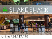 Купить «Singapore, Republic of Singapore, Asia - Customers queue in front of a Shake Shack burger restaurant at Changi Airport's Jewel terminal on the first day...», фото № 34117170, снято 6 июля 2020 г. (c) age Fotostock / Фотобанк Лори
