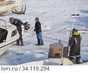 Fischerboot wird ins Wasser gezogen. Winter im Hafen der Stadt Ilulissat an der Disko Bucht in Westgroenland, Zentrum fuer Tourismus, Verwaltung und Wirtschaft. Nordamerika, Groenland, Daenemark. Редакционное фото, фотограф Martin Zwick / age Fotostock / Фотобанк Лори