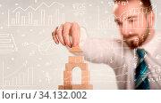 Купить «Young handsome businessman using wooden building blocks with white calculations scribbled around him», фото № 34132002, снято 7 августа 2020 г. (c) easy Fotostock / Фотобанк Лори