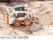 Russia Samara April 2020: Utility tractor Mini loader Bobcat S175 rakes gravel during repair of asphalt on a city street. Редакционное фото, фотограф Акиньшин Владимир / Фотобанк Лори