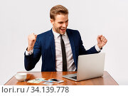 Купить «Wow thats a huge win. Attractive young blond man, businessman sitting office, looking at laptop display and smiling, clench fists relish some good news, winning, achieve goal, white background.», фото № 34139778, снято 14 июля 2020 г. (c) easy Fotostock / Фотобанк Лори