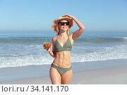 Купить «Woman with coconut cocktail standing on the beach», фото № 34141170, снято 25 февраля 2020 г. (c) Wavebreak Media / Фотобанк Лори