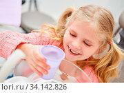 Mädchen beim Zahnarzt spült sich den Mund mit einem Becher Wasser bei der Behandlung. Стоковое фото, фотограф Zoonar.com/Robert Kneschke / age Fotostock / Фотобанк Лори
