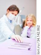 Zahnärztin oder Arzthelferin wählt ein Handinstrument aus für Untersuchung von Kind als Patient. Стоковое фото, фотограф Zoonar.com/Robert Kneschke / age Fotostock / Фотобанк Лори