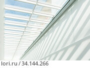 Купить «Roof Construction. Joist, rafter. Abstract contemporary architecture or modern interior photograph. Geometric shapes and patterns. Shadow on the white wall.», фото № 34144266, снято 3 июля 2020 г. (c) easy Fotostock / Фотобанк Лори