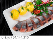 Sliced salted herring with vegetables on white plate. Стоковое фото, фотограф Zoonar.com/Ruslan Olinchuk / easy Fotostock / Фотобанк Лори