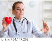Cardiologist with red heart in medical concept. Стоковое фото, фотограф Elnur / Фотобанк Лори