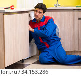 Купить «Repairman repairing washing machine in the kitchen», фото № 34153286, снято 14 июня 2018 г. (c) Elnur / Фотобанк Лори