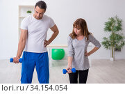 Купить «Young woman doing sport exercises with personal coach», фото № 34154054, снято 18 сентября 2019 г. (c) Elnur / Фотобанк Лори