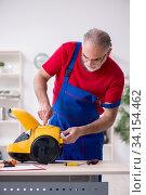 Купить «Old male contractor repairing vacuum cleaner indoors», фото № 34154462, снято 11 октября 2019 г. (c) Elnur / Фотобанк Лори