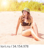Beautiful young woman enjoys the sunshine on a sandy beach. Стоковое фото, фотограф Акиньшин Владимир / Фотобанк Лори