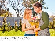 Junge Frau freut sich über Blumen von ihrem Freund im Sommer im Garten. Стоковое фото, фотограф Zoonar.com/Robert Kneschke / age Fotostock / Фотобанк Лори