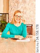 Junge Frau als Studentin mit einem Buch beim Lernen für das Studium zuhause. Стоковое фото, фотограф Zoonar.com/Robert Kneschke / age Fotostock / Фотобанк Лори