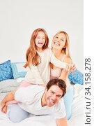 Eltern lachen und albern mit ihrer Tochter herum morgens im Bett im Schlafzimmer. Стоковое фото, фотограф Zoonar.com/Robert Kneschke / age Fotostock / Фотобанк Лори