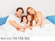 Glückliche Eltern und zwei Kinder beim Kuscheln im Bett im Schlafzimmer. Стоковое фото, фотограф Zoonar.com/Robert Kneschke / age Fotostock / Фотобанк Лори
