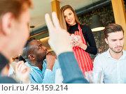 Junger Mann als Gast hebt die Hand bei einer Bestellung in einer Bar oder im Bistro. Стоковое фото, фотограф Zoonar.com/Robert Kneschke / age Fotostock / Фотобанк Лори