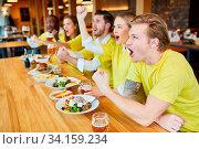 Fußballfans schauen Spiel einer Mannschaft im Restaurant oder Pub und jubeln. Стоковое фото, фотограф Zoonar.com/Robert Kneschke / age Fotostock / Фотобанк Лори