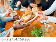 Hände verteilen Brot zur Suppe beim gemeinsamen Mittagessen oder Abendessen. Стоковое фото, фотограф Zoonar.com/Robert Kneschke / age Fotostock / Фотобанк Лори