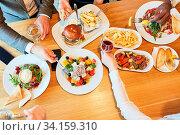Freunde beim herzhaften Mittagessen oder Abendessen zusammen im Restaurant. Стоковое фото, фотограф Zoonar.com/Robert Kneschke / age Fotostock / Фотобанк Лори