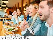 Freunde als Sportfans am Tresen einer Bar schauen Spiel einer Mannschaft. Стоковое фото, фотограф Zoonar.com/Robert Kneschke / age Fotostock / Фотобанк Лори