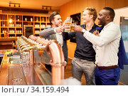 Männer trinken Bier und prosten sich zu an der Theke einer Bar oder Kneipe. Стоковое фото, фотограф Zoonar.com/Robert Kneschke / age Fotostock / Фотобанк Лори