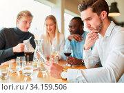 Junger Mann als Gast mit Speisekarte im Restaurant überlegt seine Bestellung. Стоковое фото, фотограф Zoonar.com/Robert Kneschke / age Fotostock / Фотобанк Лори