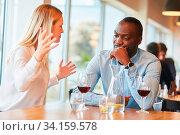 Junge Frau streitet mit ihrem afrikanischen Freund im Restaurant oder im Bistro. Стоковое фото, фотограф Zoonar.com/Robert Kneschke / age Fotostock / Фотобанк Лори