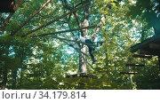 Купить «A man crossing rope construction in the forest - extreme attraction», видеоролик № 34179814, снято 12 июля 2020 г. (c) Константин Шишкин / Фотобанк Лори