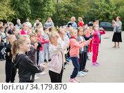 Купить «Первоклашки на дне здоровья танцуют и выполняют спортивные упражнения у стен школы», эксклюзивное фото № 34179870, снято 14 июля 2020 г. (c) Кузин Алексей / Фотобанк Лори