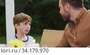 Купить «Dad and son talking to each other while having lunch outdoors», видеоролик № 34179970, снято 28 ноября 2019 г. (c) Wavebreak Media / Фотобанк Лори