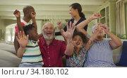 Three generation family cheering while watching TV at home. Стоковое видео, агентство Wavebreak Media / Фотобанк Лори