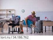 Купить «Young male employee preparing for the trip», фото № 34186762, снято 28 мая 2020 г. (c) Elnur / Фотобанк Лори