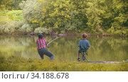Two brothers on fishing - big brother throws fishing rod in the lake. Стоковое видео, видеограф Константин Шишкин / Фотобанк Лори