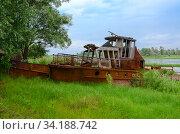 Заброшенный ржавый корабль на берегу реки в зоне отчуждения Чернобыльской АЭС, Беларусь. Стоковое фото, фотограф Ольга Коцюба / Фотобанк Лори