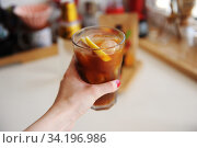 Espresso tonic with lemon slice in bid glass with ice in female hand close up. Стоковое фото, фотограф Кристина Сорокина / Фотобанк Лори
