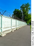 Купить «Concrete fence with barbed wire. Close-up of barbed wire. Sunny day. The concept of freedom», фото № 34197054, снято 14 июня 2020 г. (c) Григорий Стоякин / Фотобанк Лори
