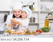 Купить «Mother and her young daughter in uniform are adding spices in salad together», фото № 34206114, снято 27 января 2018 г. (c) Яков Филимонов / Фотобанк Лори
