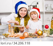Купить «Woman with her daughter are standing with dish for New Year in the kitchen», фото № 34206118, снято 27 января 2018 г. (c) Яков Филимонов / Фотобанк Лори